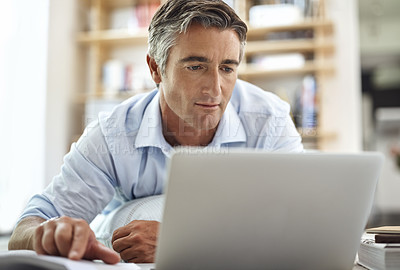 Buy stock photo Cropped shot of a handsome mature man lying on his living room floor using a laptop