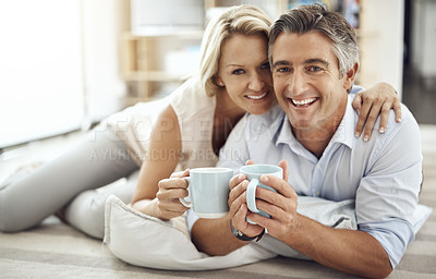 Buy stock photo Cropped portrait of an affectionate mature couple lying on their living room floor drinking coffee