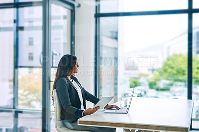 Buy stock photo Shot of a young businesswoman using a digital tablet and laptop in a modern office