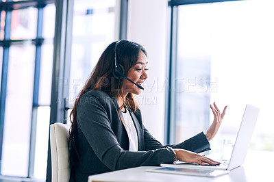 Buy stock photo Shot of a young woman using a headset and laptop in a modern office