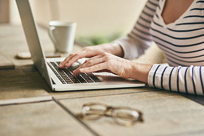 Buy stock photo Cropped shot of an unrecognizable young woman using her laptop while working in her home office