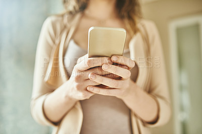 Buy stock photo Cropped shot of an unrecognizable young woman using her mobile phone while standing indoors