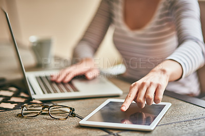 Buy stock photo Cropped shot of an unrecognizable young woman using a digital tablet while working in her home office