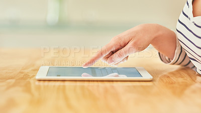 Buy stock photo Cropped shot of an unrecognizable young woman using a digital tablet while sitting on a desk at home