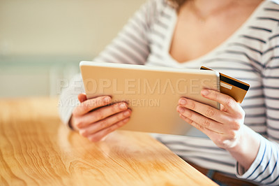 Buy stock photo Cropped shot of an unrecognizable young woman using a digital tablet and credit card to shop online