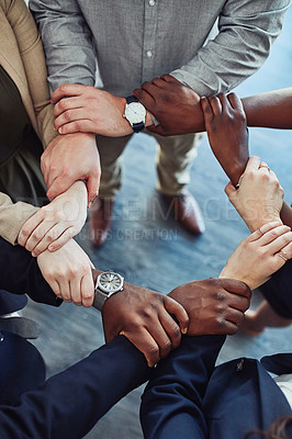 Buy stock photo Cropped shot of a group of businesspeople linking their arms in solidarity