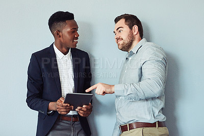 Buy stock photo Studio shot of two young businessmen using a digital tablet together against a grey background