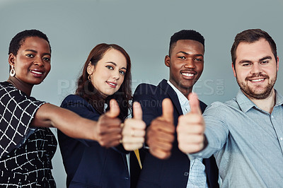 Buy stock photo Studio portrait of a group of young businesspeople giving thumbs up against a grey background