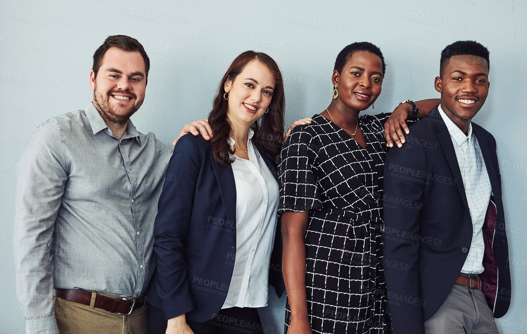 Buy stock photo Studio portrait of a group of young businesspeople embracing against a grey background