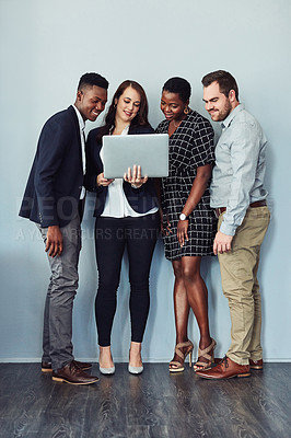Buy stock photo Studio shot of a group of young businesspeople using a laptop together against a grey background