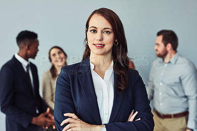 Buy stock photo Studio portrait of a confident young businesswoman standing in front of her colleagues against a grey background