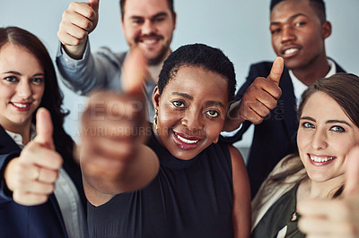 Buy stock photo High angle studio shot of a group of young businesspeople giving thumbs up against a grey background