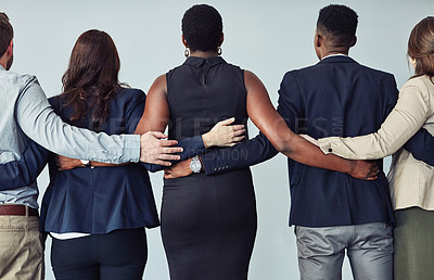 Buy stock photo Rearview studio shot of a group of young businesspeople embracing against a grey background