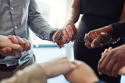 Buy stock photo Cropped shot of a group of businesspeople standing together and holding hands in a modern office