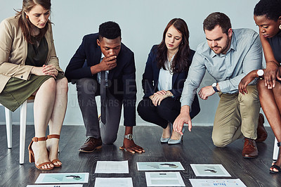 Buy stock photo Studio shot of a group of young businesspeople going through paperwork together on the floor