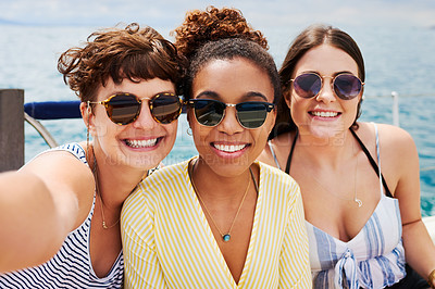 Buy stock photo Shot of a group of happy young women taking selfies on a cruise