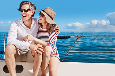 Buy stock photo Cropped shot of an affectionate mature couple enjoying a boat cruise out on the ocean