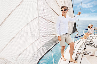 Buy stock photo High angle shot of a handsome mature man enjoying a boat cruise out on the ocean with his wife in the background