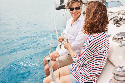 Buy stock photo High angle shot of an affectionate mature couple enjoying a boat cruise out on the ocean