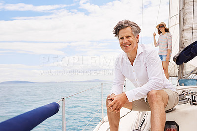 Buy stock photo Cropped portrait of a handsome mature man enjoying a boat cruise out on the ocean with his wife in the background