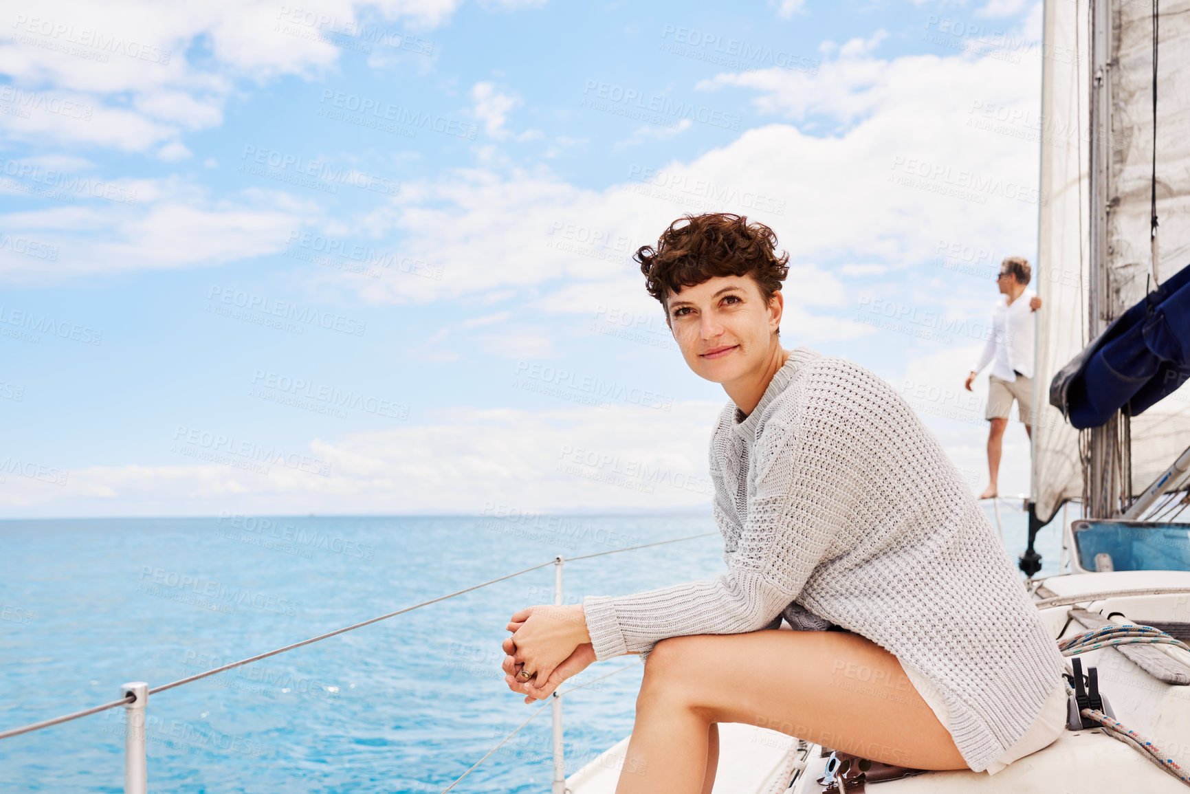 Buy stock photo Cropped portrait of an attractive mature woman enjoying a boat cruise out on the ocean with her husband in the background