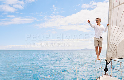 Buy stock photo Full length shot of a handsome mature man enjoying a boat cruise out on the ocean