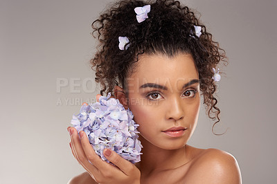 Buy stock photo Studio portrait of a beautiful young woman posing with a bunch of flowers against a grey background