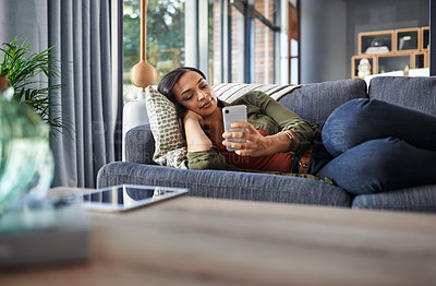 Buy stock photo Shot of a beautiful young woman using her phone while lying down on a couch at home