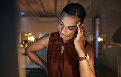 Buy stock photo Shot of a beautiful young businesswoman suffering from a headache while working late in her office during the evening