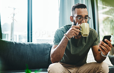 Buy stock photo Shot of a young man using a smartphone and having coffee on the sofa at home