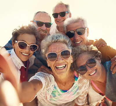 Buy stock photo Cropped shot of a group of senior friends taking selfies while enjoying their day out on the beach