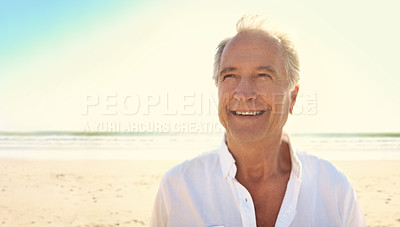 Buy stock photo Cropped shot of a handsome senior man enjoying his day out at the beach