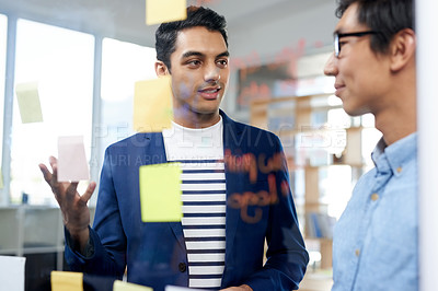 Buy stock photo Shot of two businessmen brainstorming with notes on a glass wall in an office