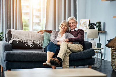 Buy stock photo Cropped portrait of an affectionate senior couple sitting on their living room sofa at home