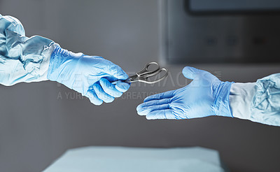 Buy stock photo Cropped shot of an unrecognizable surgeon passing his colleague a pair of scissors