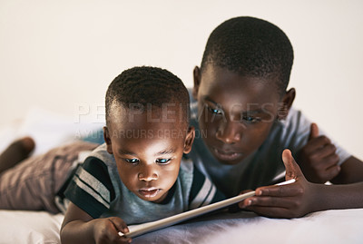 Buy stock photo Shot of two young boys using a digital tablet together at night in bed