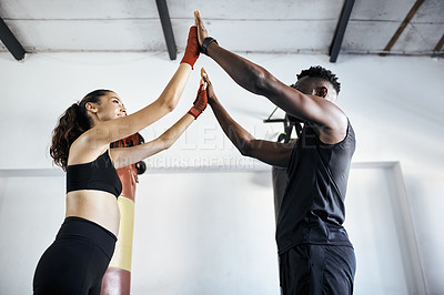 Buy stock photo Shot of a young sportswoman working out with her fitness coach at the gym