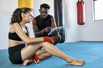 Buy stock photo Full length shot of a fitness coach using a digital tablet while training a sportswoman at the gym