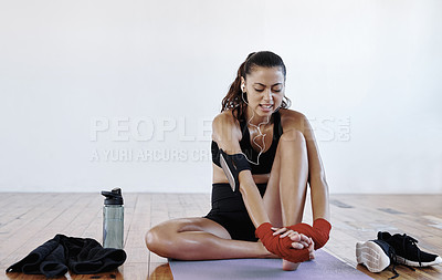 Buy stock photo Full length shot of a young sportswoman sitting down and experiencing discomfort on her foot while working out indoors