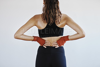 Buy stock photo Rearview shot of a sportswoman suffering from back pain against a grey background