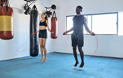 Buy stock photo Full length shot of two young sportspeople working out using a skipping rope at the gym