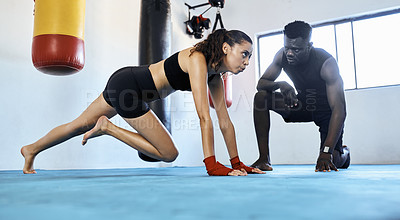 Buy stock photo Full length shot of a young sportswoman working out with her fitness coach at the gym