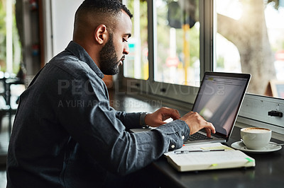 Buy stock photo Cropped shot of a handsome young man using a laptop while sitting in a cafe