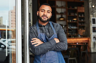 Buy stock photo Portrait of a confident business owner standing in the doorway of his cafe