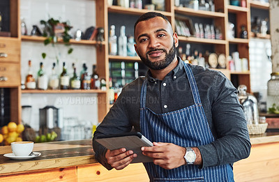 Buy stock photo Shot of a shop owner using a digital tablet in his cafe