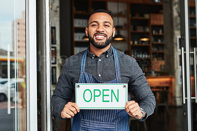 Buy stock photo Cropped shot of a coffee shop owner hold up an open sign in his doorway