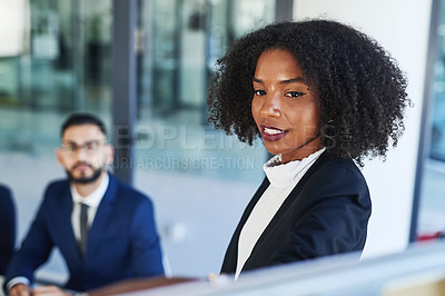Buy stock photo Shot of a beautiful young businesswoman explaining her ideas during a boardroom meeting with colleagues