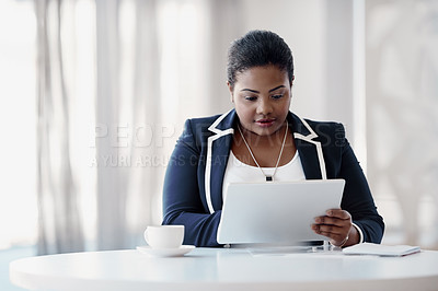 Buy stock photo Cropped shot of an attractive young businesswoman using her tablet while sitting in the office