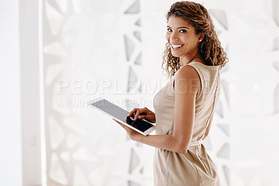 Buy stock photo Cropped portrait of an attractive young businesswoman using her tablet while standing in the office