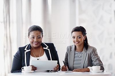 Buy stock photo Cropped portrait of two attractive young businesswomen working together behind a desk in their office